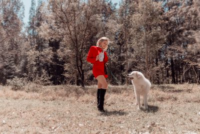 Woman in red dress grinning at a white dog