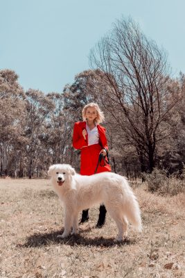 Woman in red dress posing behind white dog