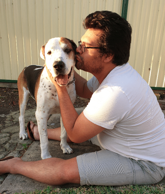 Man in glasses kissing dogs face